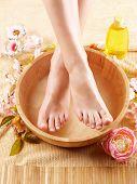 Close-up de pies hermosos femeninos en cuenco de madera lleno de cosméticos líquidos, flores alrededor. Co