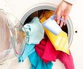 Close-up on female hand adding washing powder to washing machine full of coloful clothes