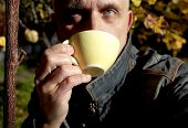 A Man Enjoying Tea Or Coffee While Sitting In A Garden, Contrast Outdoor Portrait poster
