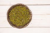 Lot Of Whole Dry Green Mung Beans In Old Iron Bowl Flatlay On White Wood poster