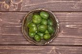 Lot Of Whole Fresh Green Mini Baby Kiwi Fruit In Old Iron Bowl Flatlay On Brown Wood poster