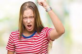 Young caucasian beautiful woman over isolated background angry and mad raising fist frustrated and f poster