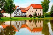 Fachwerk-Haus und Reflexion im Teich