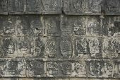 stock photo of gruesome  - Carving Detail of Gruesome Heads Decorating the Platform of Skulls Tzompantli Chichen Itza Toltec Maya Ruins Yucatan Peninsula Mexico 2007 NR - JPG