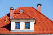 Flashing orange tiled roof on blue sky
