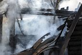 Conflagration. Ruins And Remains Of A Burnt Wooden House. Burnt Charred Firewood In Thick Smoke. poster