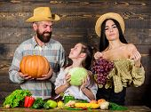 Parents And Daughter Celebrate Harvest Holiday Pumpkin Vegetables Fruits. Harvest Festival Concept.  poster