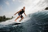 Active Man Riding On The White Wakeboard On The Wave Having Healthy Summertime On The River On The B poster