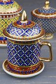 Thai Fine Art Traditional Five Colors (bencharong) Tea Cup Over Blue Blurry Background. poster