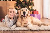 Happy Kid And Golden Retriever Dog Lying Near Christmas Tree With Gifts At Home poster