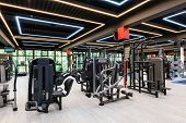Modern and stylish gym interior with equipment, some motion blurred unrecognizable persons poster
