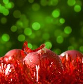 Christmas background; red bulbs, tinsel and green glittering lights