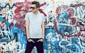 stock photo of attitude boy  - young man posing in front of a colorful graffiti wall - JPG