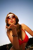 stock photo of pretty girl  - Young beautiful woman in sunglasses blow a kiss to you - JPG
