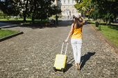 Back Rear View Traveler Tourist Woman In Yellow Summer Casual Clothes Hat With Suitcase Walking In C poster