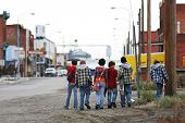 group of young skater kids with skateboards heading home, blurred background with copyspace.