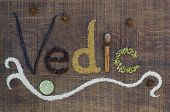 The Word Vedic Spelled Out In Ayurveda Spices And Seeds On A Wooden Countertop
