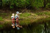 stock photo of fishermen  - Little girls are fishing on lake in forest - JPG