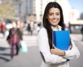 young woman smiling and holding a notebook against a street background
