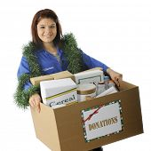 An attractive young volunteer holding a large box of food donated for the holidays.  On a white back