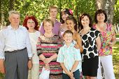 Family of nine people pose at park near big tree