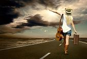 image of guitarists  - Young woman with guitar on the road and her vintage baggage - JPG