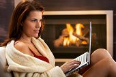Winter portrait of sexy young woman using laptop computer in bathrobe and red bra in front of firepl
