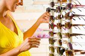 Junge Frau bei Optiker mit Brille, ist sie Kunde im Shop und kaufen einige Sonnenbrillen