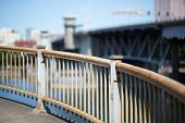 Curved steel railing with soft focus bridge and sky in Portland Oregon