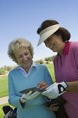 Two female friends writing their golf scores on scorecard