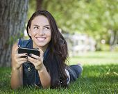 Attractive Happy Mixed Race Young Female Texting on Her Cell Phone Outside Laying in the Grass.