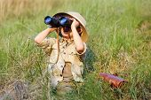 stock photo of safari hat  - Young boy child playing pretend explorer adventure safari game outdoors with binoculars and bush hat - JPG