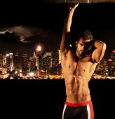 Sexy muscular young shirtless man at night with city lights and skyline in background with copy spac