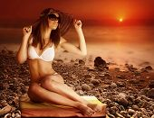 Sexy tanned model posing on the beach on red dramatic sunset background, stony coastline, fog over s