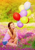 Pretty girl sitting down on pink floral meadow and holding in hands colorful balloons, having fun outdoors, summer vacation concept