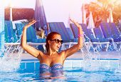 Happy pretty girl having fun in the pool, cute playful female splashing water in swimming pool, rela