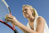 Low angle view of a female tennis player preparing to serve against clear blue sky