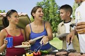 Boy with family gathered around the grill at picnic