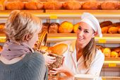 Female baker or saleswoman in her bakery with a female customer and fresh pastries or bakery product