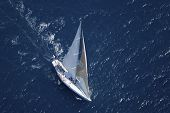 Top view of a sailboat in the peaceful blue ocean