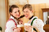 Two young women in traditional Bavarian Tracht in restaurant or pub with beer and beer stein
