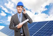Smiling engineer in front of solar panels