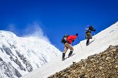 stock photo of snow clouds  - Two mountain backpackers walking on snow with peaks background Himalayas - JPG