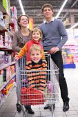 Parents With Children In Cart In Shop