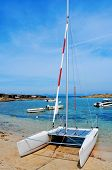 a sailboat and the Mediterranean Sea in Cala Sa Roqueta cove, in Formentera, Balearic Islands, Spain