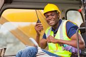 cheerful african bulldozer operator talking on walkie talkie on construction site