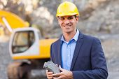 happy manager in mining site holding ore