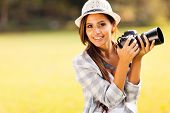 cheerful attractive woman holding a camera outdoors