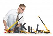 Building up skills concept: Focused businessman building the word skill along with construction machines, isolated on white background.