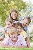 Vijf jonge vrienden opgestapeld op elkaar buiten glimlachen